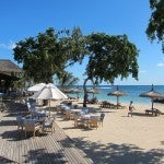 The beach at the Grand Mauritian with shaded palapas.