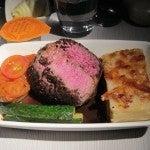 Pan-seared prime beef tenderloin with rosemary jus, potato gratin, stuffed eggplant and baby zucchini.