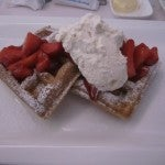 Waffles with whipped cream and fresh strawberries for breakfast.