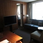 The living room of a Park Suite King with armchair, loveseat, work desk and TV.