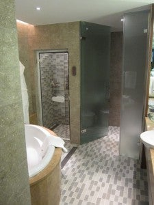 The spacious bathroom of a Park Suite King with deep soaking tub, separate rainfall shower and limestone features.