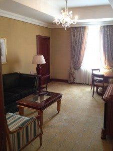 The living room of our suite with a small sitting area and coffee table, breakfast table, and chest with a Band & Olufsen flat-screen TV on top.