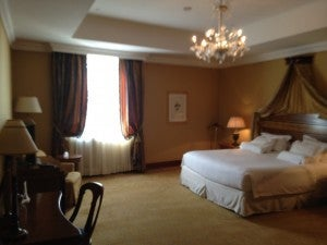 The master bedroom of the suite with a king-size bed and work desk and anothe flat-screen TV.
