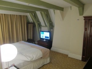 The master bedroom in my duplex suite with king-size bed, its own flat-screen and cheerful bright green beams.