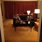 The living room of my Statesman suite with a couple couches, coffee table, work desk, and fruit and water welcome amenity.