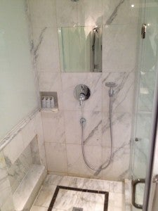 The separate marble shower with fog-proof mirror and fancy Remede bath products.