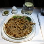 A mid-flight snack of noodles with vegetables and chicken.
