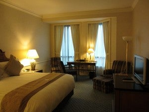 The standard room with king-size bed, flatscreen, and small sitting area with table, chair and armchair.