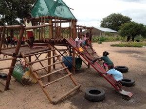 The kids playing around on the playground set.