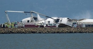 Fire trucks subdue the flames at the Asiana crash scene (AP Photo/Noah Berger).