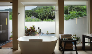 Looking out through the bathroom to the private patio of the King Beachfront Villa, including an outdoor rain shower and private plunge pool.