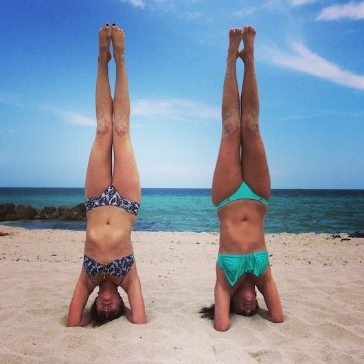 Practicing handstands on the beach with my friend Betsy (left)