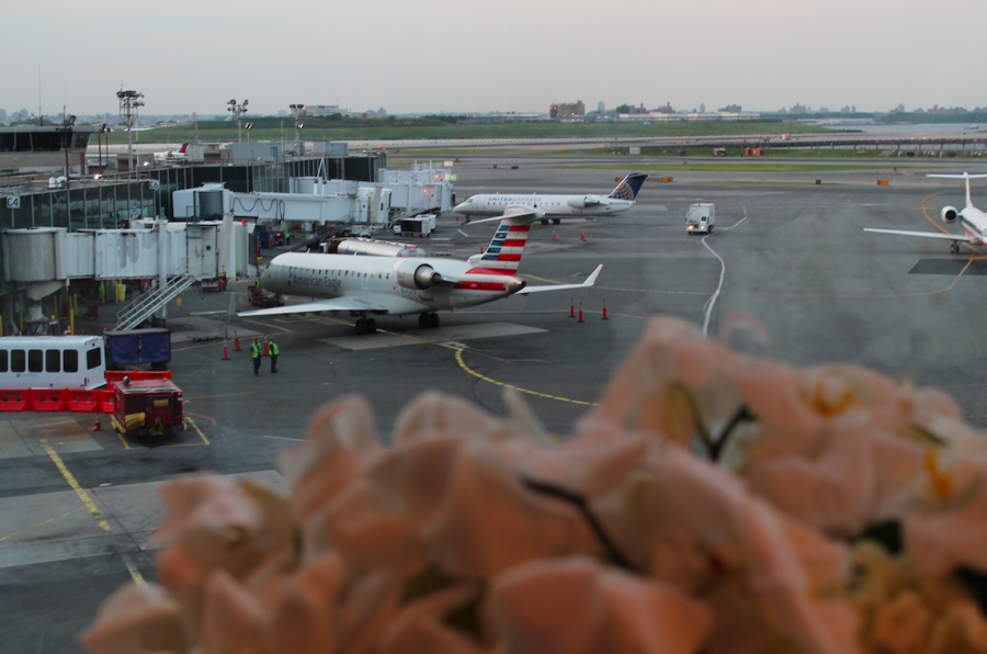 Fresh flowers and a view of the planes on the tarmac and the runway in the distance
