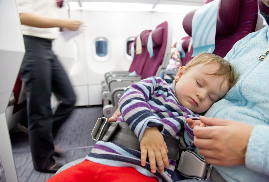 Most airlines allow children under two to be seated on the lap. Photo courtesy of Shutterstock.