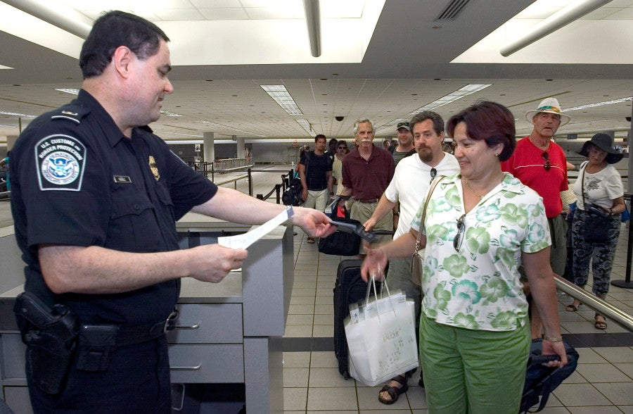 A CBP officer checks a passenger's documentation after arriving to the US. Courtesy DHS.