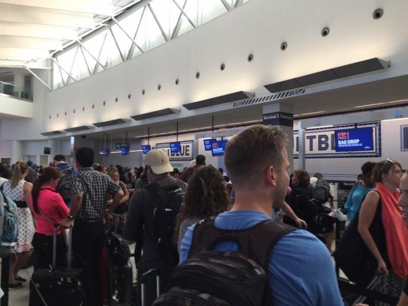 Linea di riconsegna bagagli sovraffollata del Terminal 5's over crowded baggage drop line