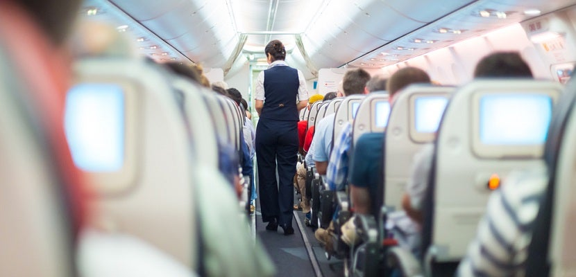 Airplane aisle attendant featured shutterstock 253704592