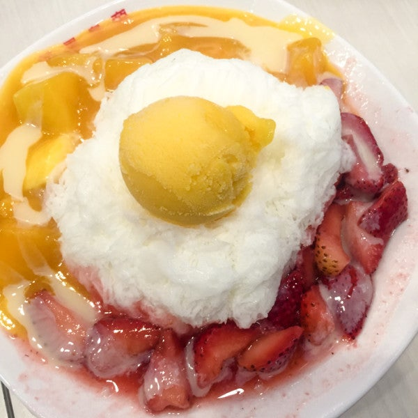 Shaved snow cream topped with mango ice cream, surrounded by fresh mangoes and strawberries, all drizzled with condensed milk.