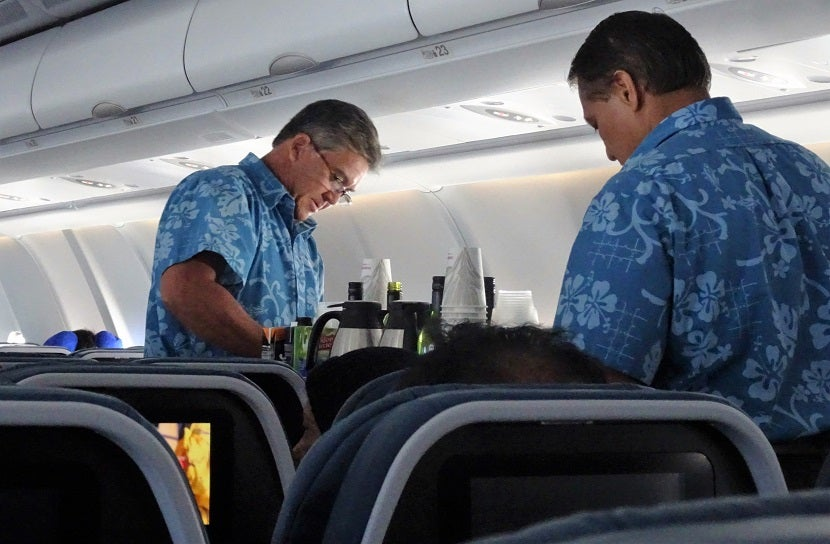 Flight Attendants In Tropical Garb Serve Drinks