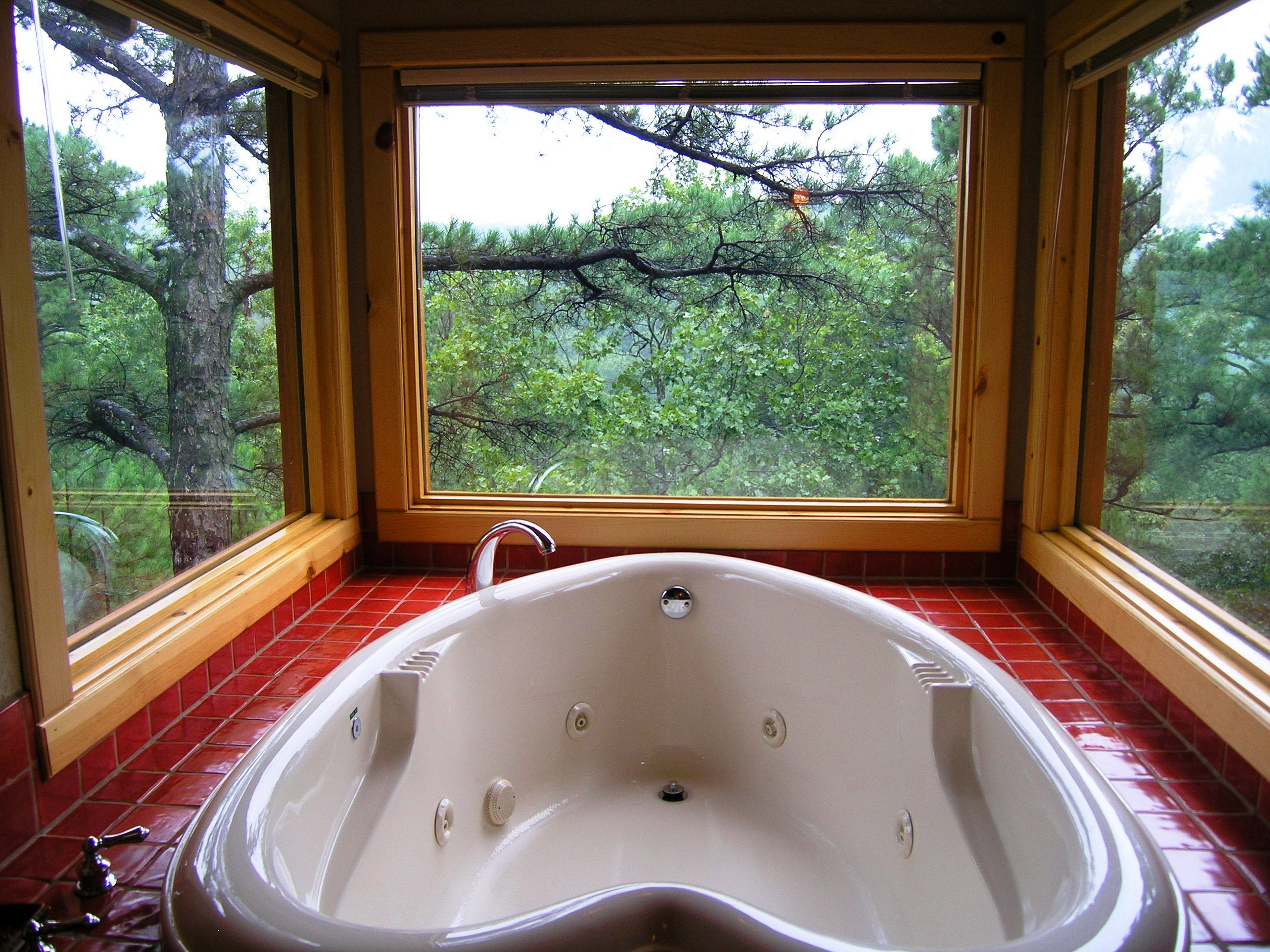 A Double Size Heart Shaped Jacuzzi Is Positioned In Front Three Large  Windows.
